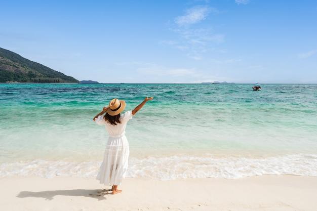 Giovane donna viaggiatrice che si rilassa e si diverte in una bellissima spiaggia tropicale di sabbia bianca con schiuma d'onda e mare trasparente, vacanze estive e concetto di viaggio