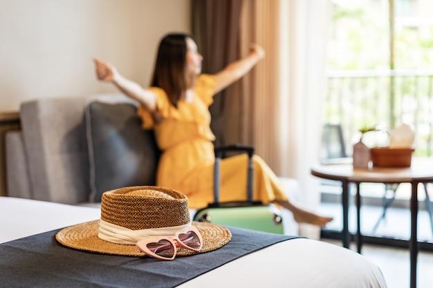 Viaggiatore della giovane donna seduto e rilassante in una camera d'albergo durante le vacanze estive, concetto di stile di vita di viaggio