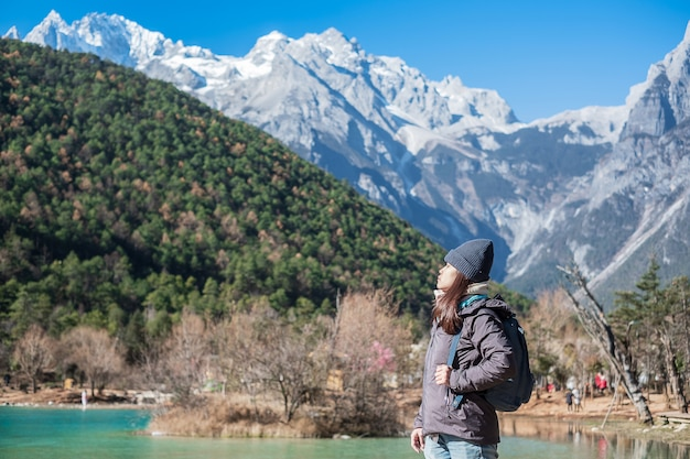 Viaggiatore di giovane donna che viaggia a blue moon valley, punto di riferimento e luogo popolare all'interno di jade dragon snow mountain scenic area, vicino a lijiang old town. lijiang, yunnan, cina. concetto di viaggio solista