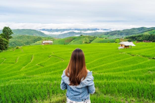 Viaggiatore della giovane donna in vacanza godendo e guardando il bellissimo campo di terrazze di riso verde in pa pong pieng, chiangmai thailandia