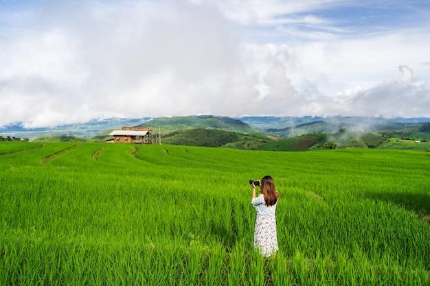 Viaggiatore di giovane donna in vacanza a scattare una foto al bellissimo campo di terrazze di riso verde in thailandia