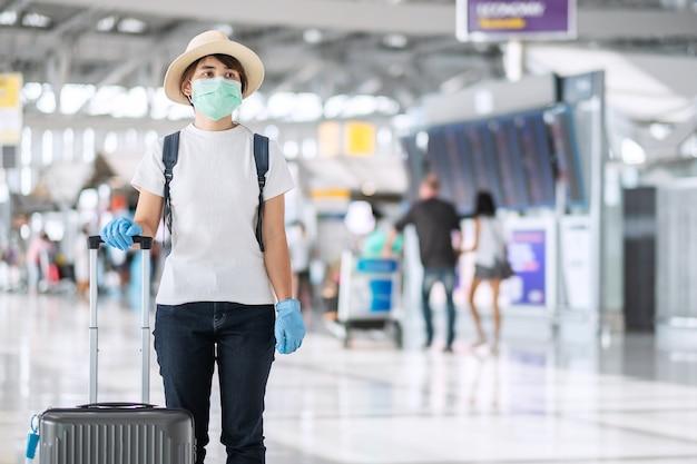 Viaggiatore di giovane donna che indossa maschera facciale e guanto di nitrile che tiene i bagagli con maniglia nel terminal dell'aeroporto, protezione dalla malattia da coronavirus (covid-19). nuovo concetto di bolla normale e di viaggio
