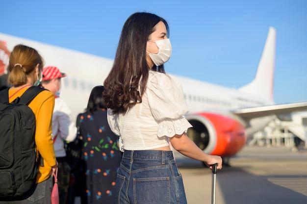 Una giovane viaggiatrice che indossa una maschera protettiva che sale in aereo e pronta al decollo, viaggia sotto la pandemia covid-19, viaggi di sicurezza, protocollo di allontanamento sociale