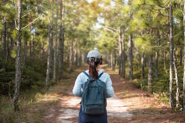 Giovane donna viaggiatrice con un casco e uno zaino che cammina attraverso una foresta