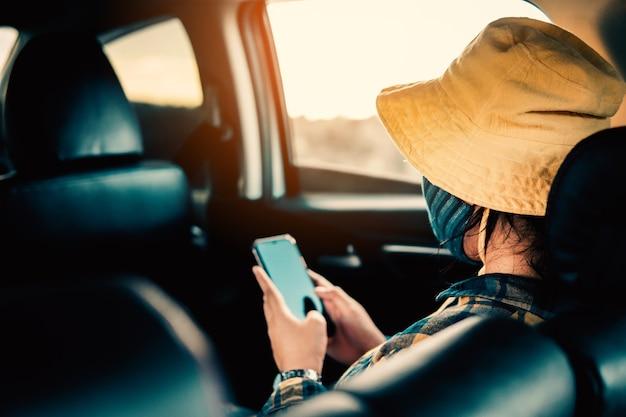 Giovane donna che viaggia in vacanza con la macchina e indossa la maschera per proteggere covid 19