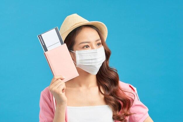 Giovane donna che indossa una maschera facciale in cotone fatta a mano con passaporto e biglietto su sfondo blu. concetto di viaggio durante il coronavirus.