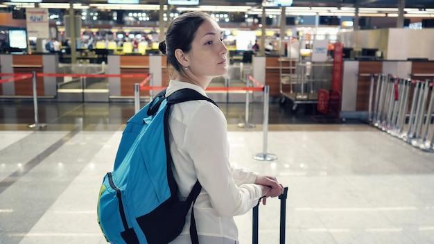 Viaggiatore della giovane donna con lo zaino e la valigia nell'edificio del terminal dell'aeroporto, primo piano. lei è in piedi e si guarda intorno, vista posteriore.