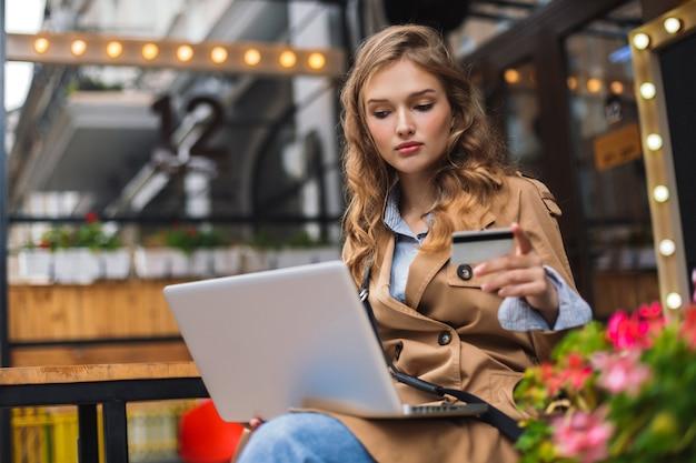 Giovane donna in trench che tiene la carta di credito in mano sognante lavorando al laptop mentre trascorre del tempo all'aperto presso l'accogliente terrazza del caffè