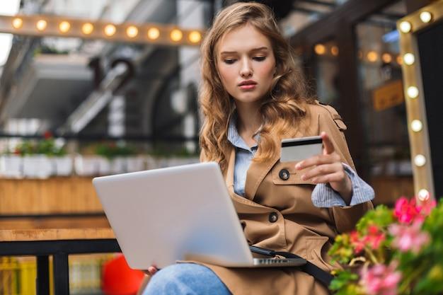 Giovane donna in trench che tiene la carta di credito in mano minuziosamente lavorando al computer portatile mentre trascorre del tempo all'aperto presso la terrazza del caffè