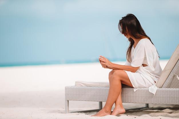 Giovane donna su una spiaggia tropicale con cappello