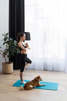 Giovane donna che cerca di fare sport a casa con il suo cane