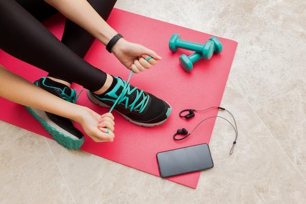 Una giovane donna che lega i lacci delle scarpe a casa in salotto per il fitness