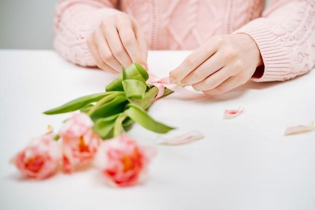 Giovane donna che lega un nastro su un mazzo di tulipani rosa. messa a fuoco selettiva, sfondo bianco, spazio di copia del testo.