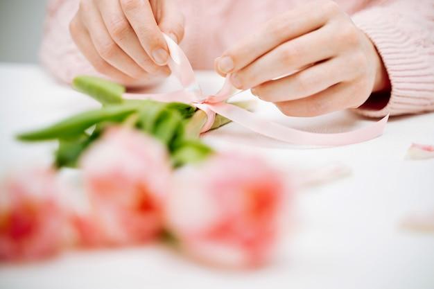 Giovane donna che lega un nastro su un mazzo di tulipani rosa. messa a fuoco selettiva, sfondo bianco, spazio per la copia del testo.