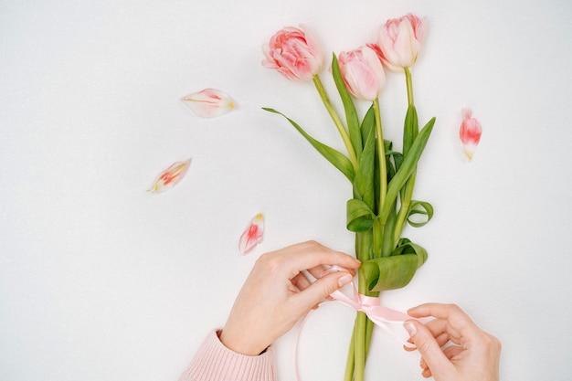 Giovane donna che lega un nastro su un mazzo di tulipani rosa. vista dall'alto, sfondo bianco, spazio per la copia del testo.