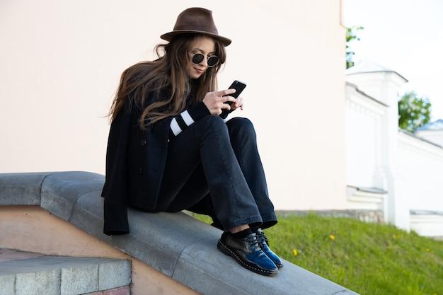 Giovane donna che scrive sul suo telefono. stile di strada