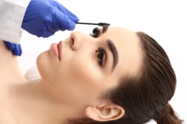 Giovane donna che subisce la procedura di correzione delle sopracciglia nel salone di bellezza