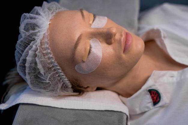 Giovane donna sottoposta a procedura di laminazione delle ciglia nel salone di bellezza, primo piano