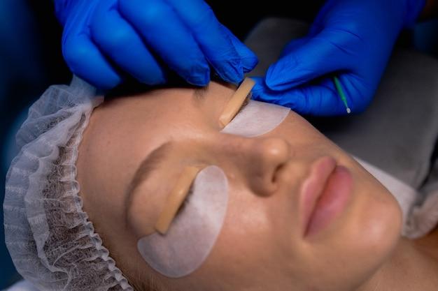 Giovane donna sottoposta a procedura di laminazione delle ciglia nel salone di bellezza