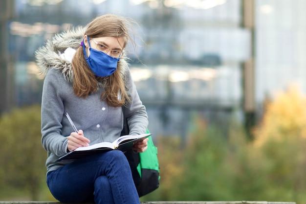 Giovane donna, università o studentessa di college sta studiando, leggendo un libro all'aperto nel campus