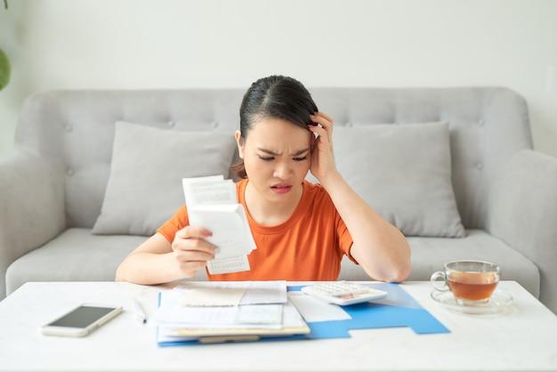 La giovane donna usa la calcolatrice analizza le spese controlla le bollette