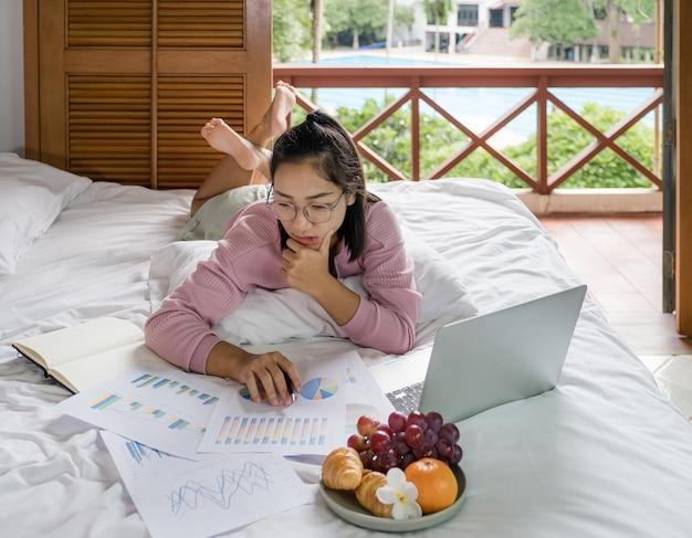 La giovane donna utilizzava videoconferenze con laptop e mangiava frutta a letto cibo sano e lavorava da casa