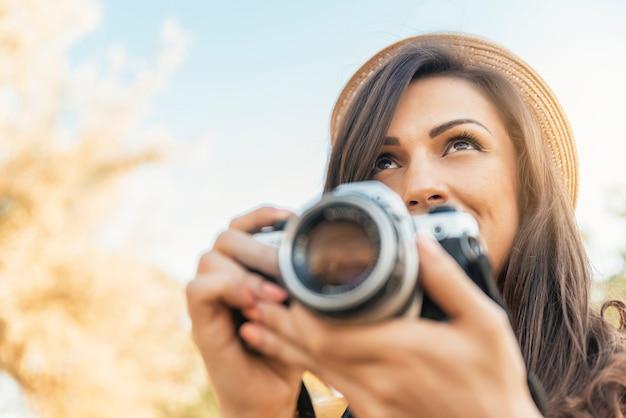 Giovane donna che utilizza una fotocamera per scattare foto al parco.