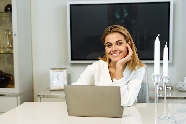 Giovane donna utilizzando il computer portatile nel suo soggiorno e guardando la telecamera. libero professionista femminile che lavora a casa.