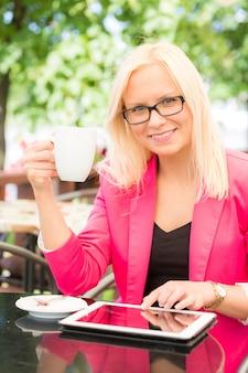 Giovane donna che utilizza la compressa digitale al caffè