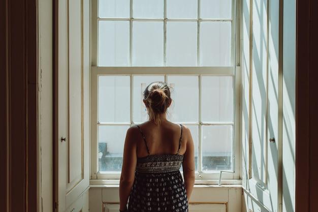 Giovane donna che usa un vestito guardando attraverso una finestra, dando le spalle alla telecamera, concetti di stress e ansia, immagine scura, tristezza