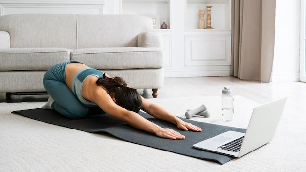 Giovane donna che utilizza un tappetino fitness per allenarsi