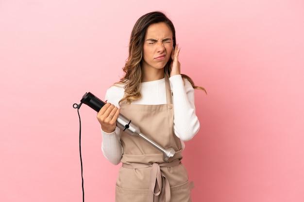 Giovane donna che usa il frullatore a immersione su sfondo rosa isolato frustrata e che copre le orecchie