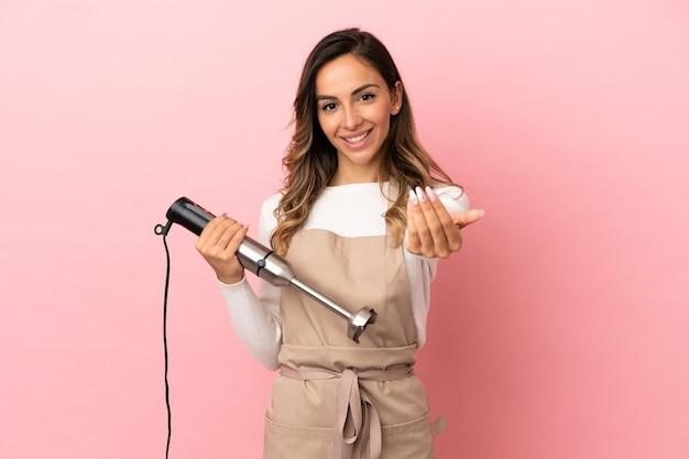 Giovane donna che utilizza frullatore a immersione su sfondo rosa isolato che invita a venire con la mano. felice che tu sia venuto