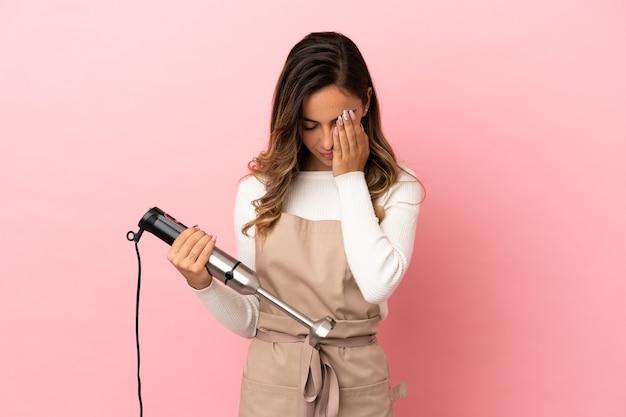 Giovane donna che utilizza frullatore a immersione su sfondo rosa isolato con espressione stanca e malata