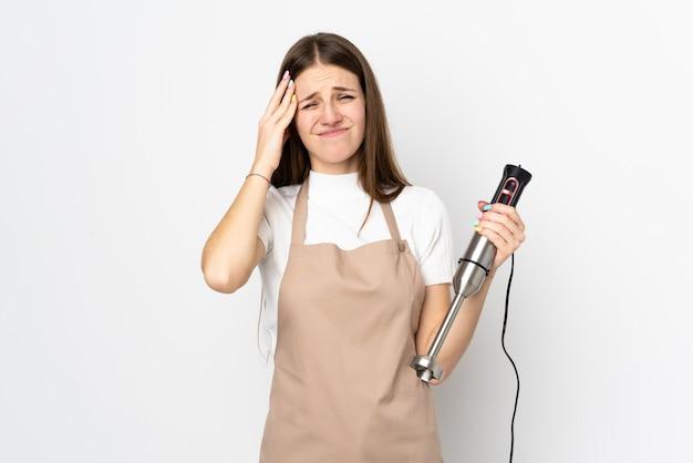 Giovane donna che usando il frullatore a immersione sulla parete bianca infelice e frustrata con qualcosa.