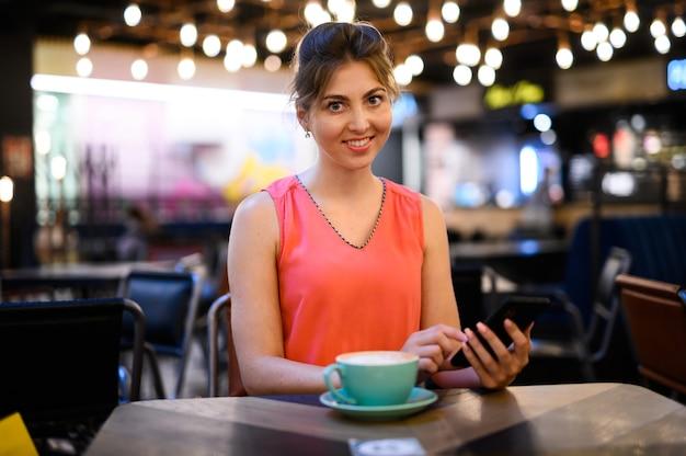 Giovane donna che usa il suo smartphone per sfogliare contenuti web e inviare messaggi mentre prende un caffè in un bar