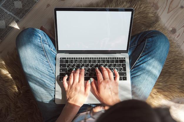 Giovane donna che utilizza lo schermo vuoto del laptop per lavorare, seduta sul pavimento a casa. orari flessibili e lavoro a distanza.