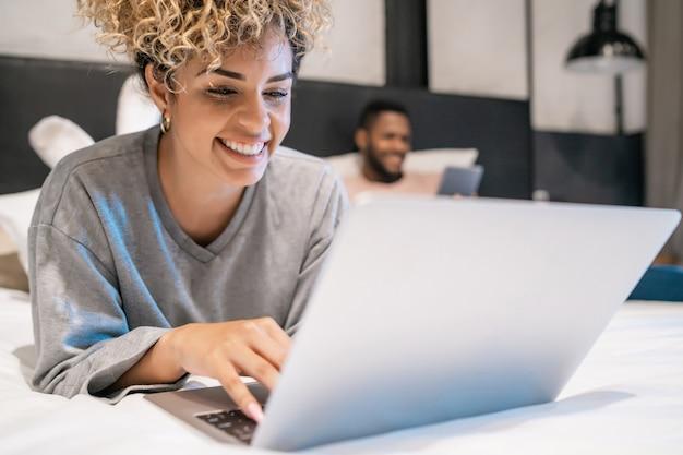 Giovane donna che usa un laptop e il suo ragazzo che usa una tavoletta digitale mentre sono a letto insieme.