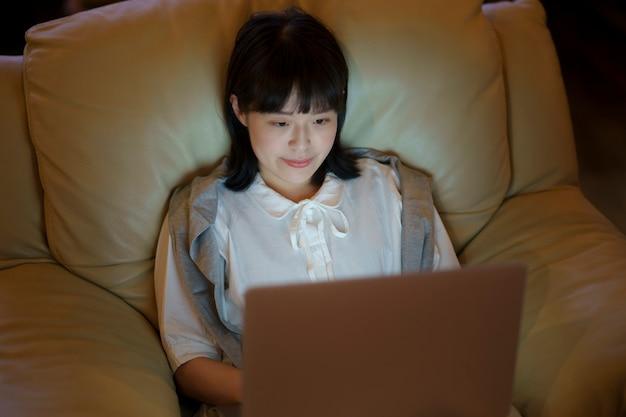 Una giovane donna che usa un laptop sul divano in una stanza con scarsa illuminazione