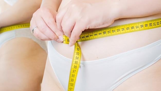 Giovane donna che utilizza nastro di misurazione per misurare il suo stomaco.