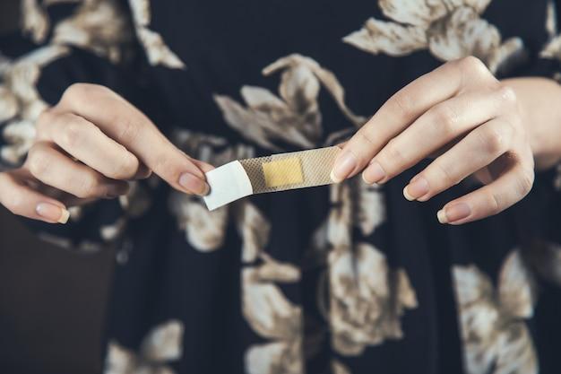 Giovane donna utilizzando cerotto medico sul dito