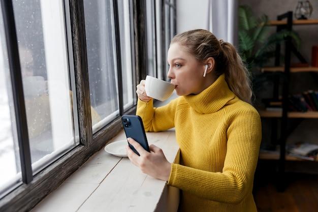 Giovane donna che utilizza il telefono cellulare e le cuffie per leggere le notizie a casa con una tazza di caffè. foto di alta qualità