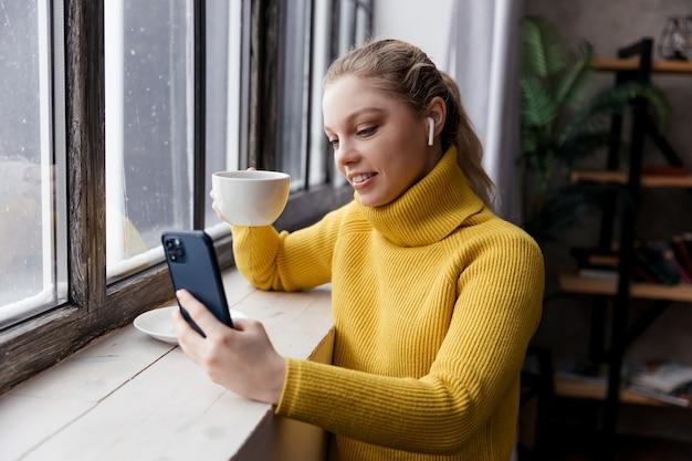 Giovane donna utilizzando il telefono cellulare e le cuffie durante il soggiorno a casa con una tazza di caffè. foto di alta qualità