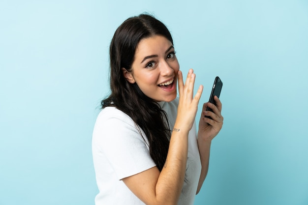 Giovane donna che utilizza il telefono cellulare isolato su sfondo blu sussurrando qualcosa