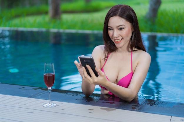 Giovane donna che utilizza il telefono cellulare in piscina