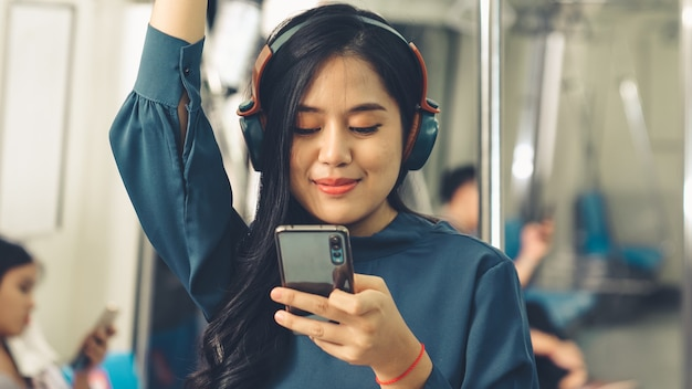 Giovane donna utilizzando il telefono cellulare sul treno pubblico