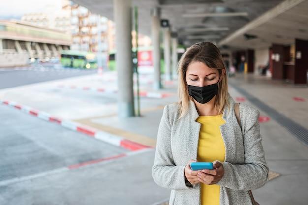 Giovane donna che utilizza il telefono cellulare mentre aspetta alla stazione degli autobus durante l'epidemia di coronavirus - focus sul viso