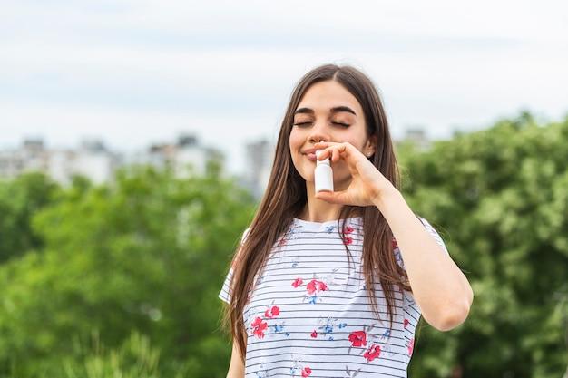 Giovane donna che utilizza spray per il naso per le sue allergie ai pollini e all'erba