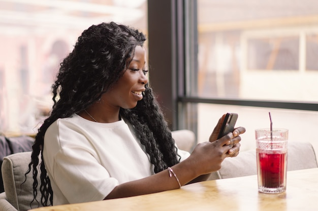Giovane donna che utilizza il telefono nella caffetteria
