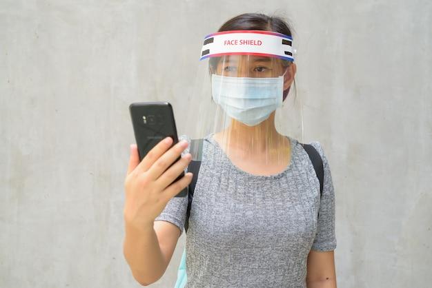 Giovane donna che utilizza il telefono con maschera e schermo facciale per la protezione dall'epidemia di virus corona all'aperto